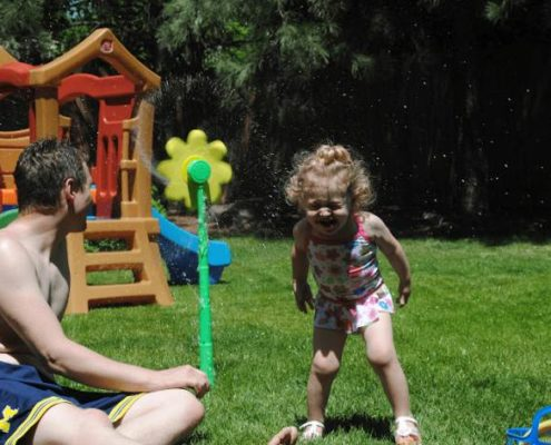 Father and daughter playing in sprinkler
